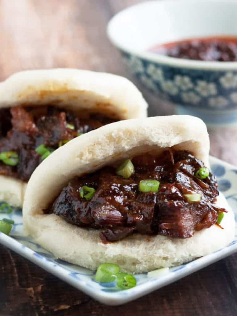 Low angle shot of two Chinese steamed buns filled with char siu pork on a rectangular plate.