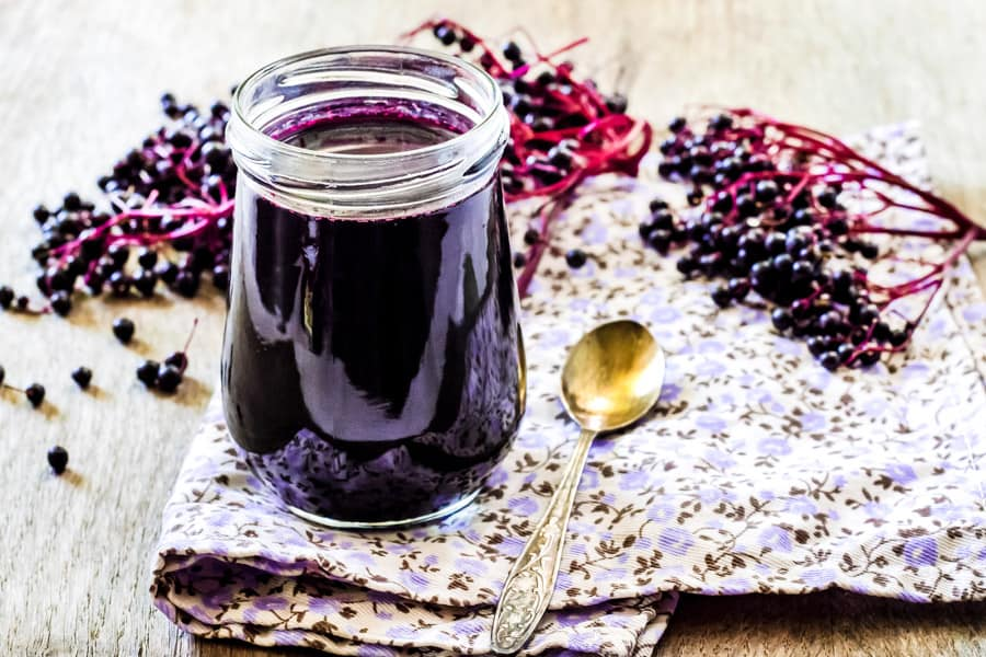 elderberry syrup in a jar sitting on an flowered napkin with an spoon and fresh elderberries shot from a low angle