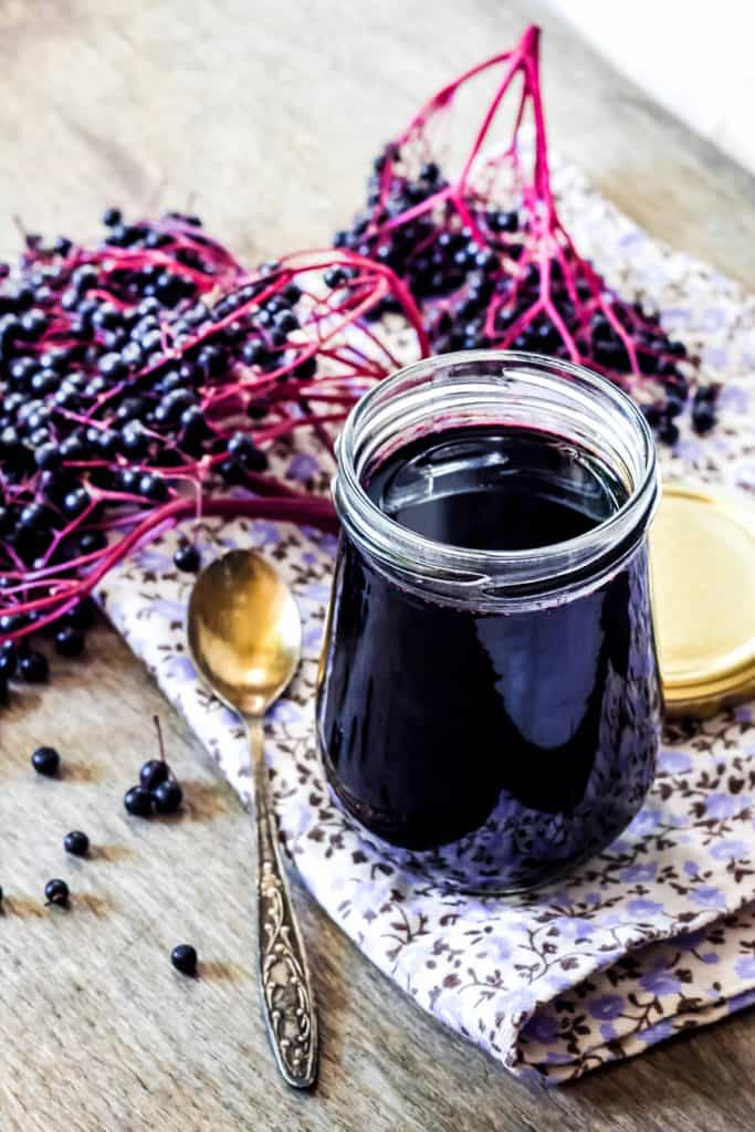 elderberry syrup in a jar sitting on an flowered napkin with an spoon and fresh elderberries
