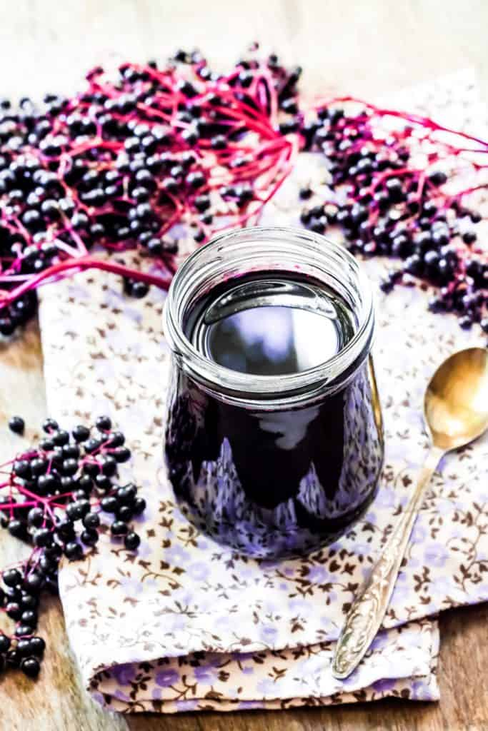 elderberry syrup in a jar with an antique spoon, fresh elderberries, and a flowered napkin