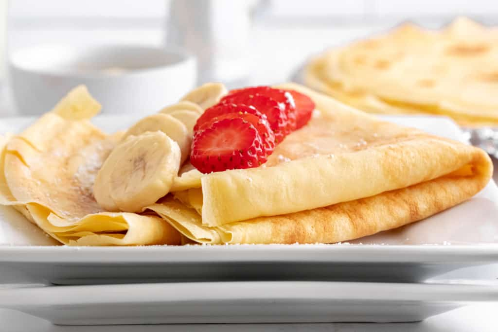 Low angle shot of a crepe folded up on a white plate with sliced banana and strawberry on top.