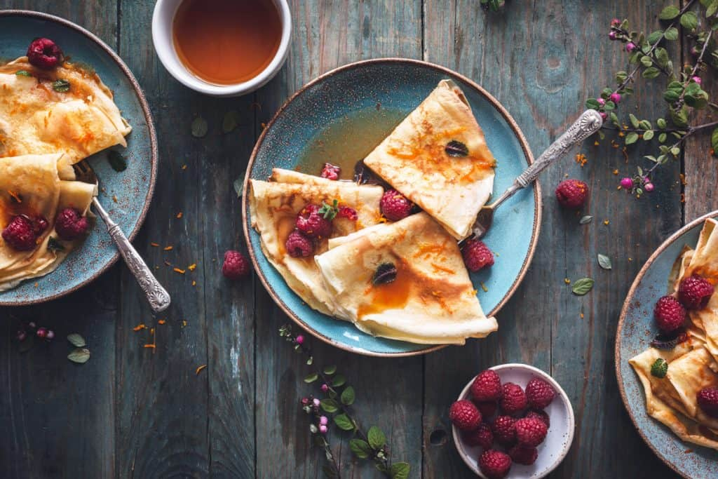 overhead photo of crepes on a blue plate with syrup. A bowl of raspberries is on the side