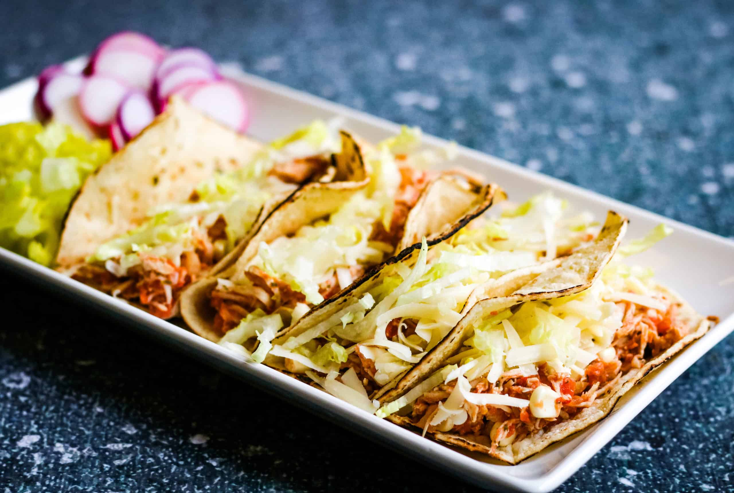 Low angle shot of 4 shredded chicken tacos in soft corn tortillas on a rectangular white plate. There is a pile of shredded lettuce and some sliced radishes on the plate.