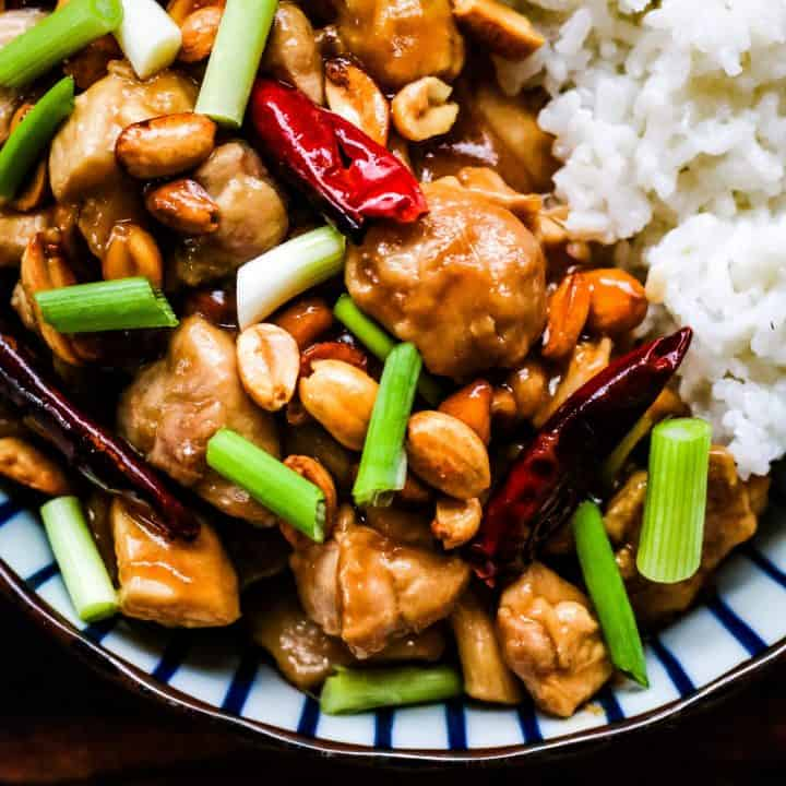 kung pao chicken in a blue and white striped bowl. There are chunks of chicken stir fried with chilies, peanuts, scallions and a savory sauce. There is cooked white rice on the side.