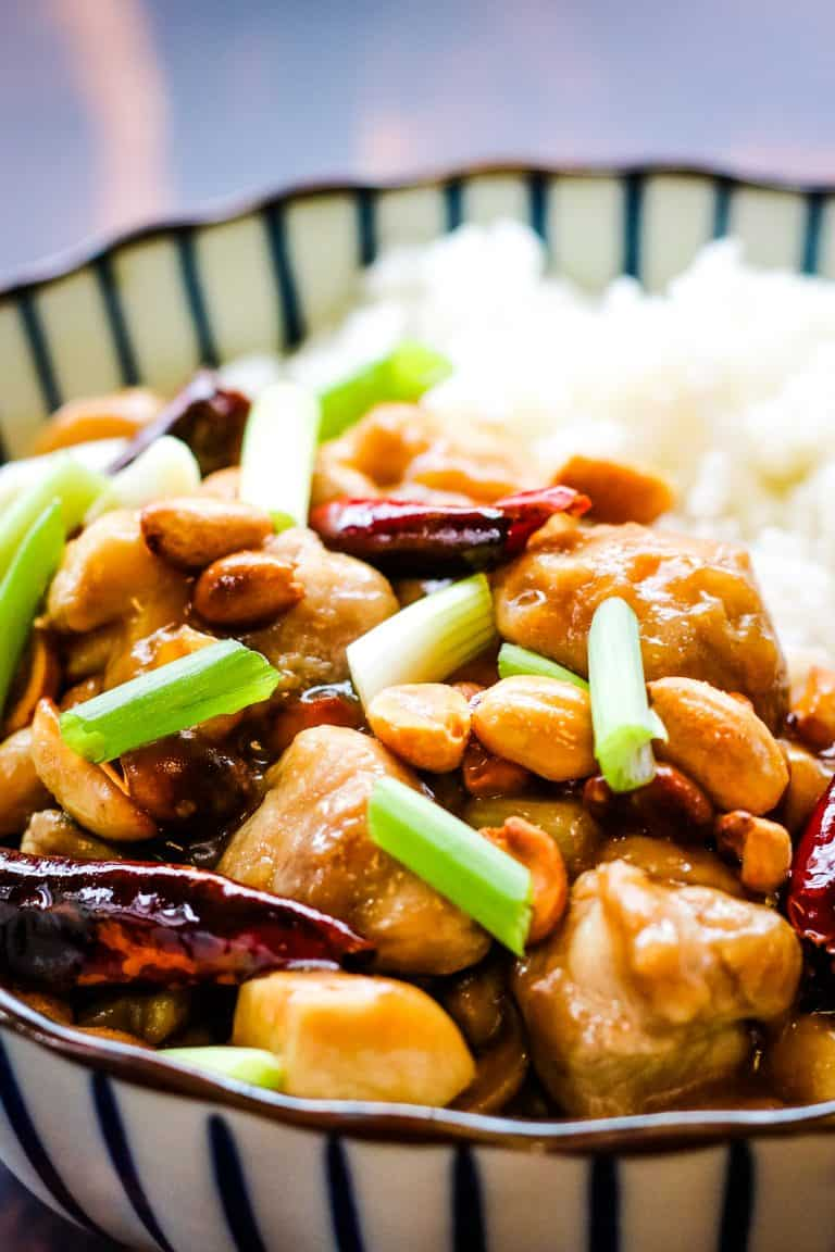 vertical photo of kung pao chicken in a blue and white striped bowl. The chicken is cooked with red chiles, scallions, and peanuts and served alongside white rice.