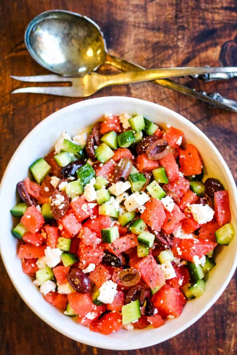 overhead shot of watermelon salad with cucumbers, feta cheese, and olives in a white bowl with silver salad servers on the table above the bowl.