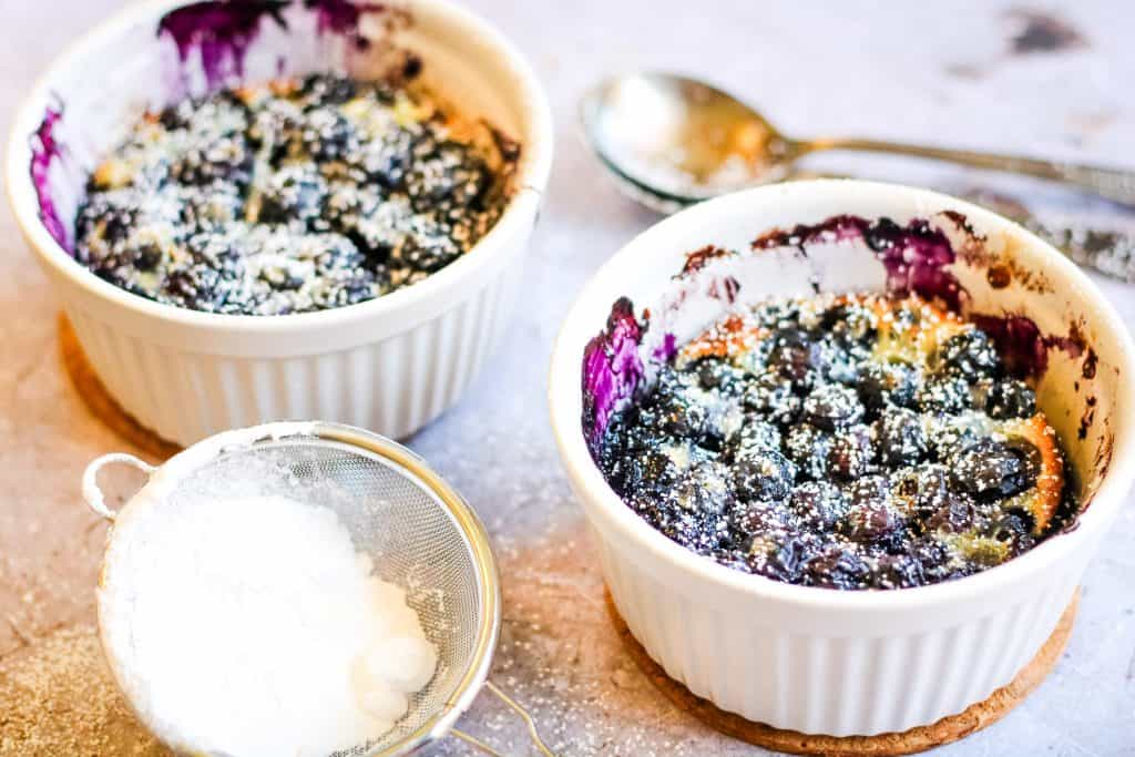 horizontal photo of blueberry clafoutis cooked in two small, white ramekins. They are sprinkled with powdered sugar and there are two spoons and a sieve with powdered sugar on the table next to the ramekins.