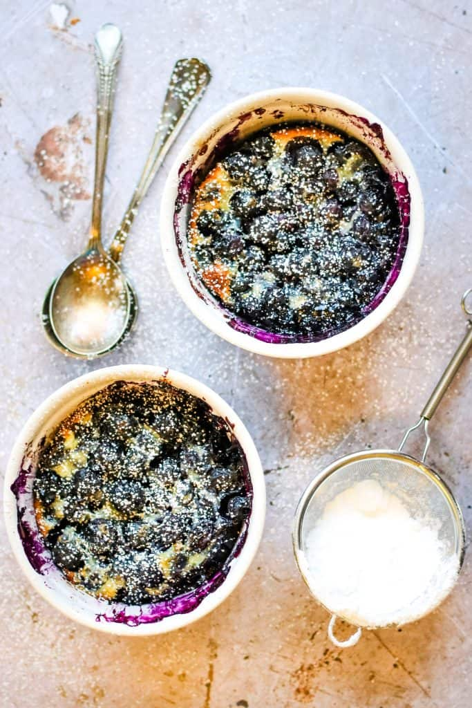 Overhead shot of two white ramekins with blueberry clafoutis topped with powdered sugar. On the table next to the ramekins are two silver spoons stacked and a sieve with powdered sugar in it.