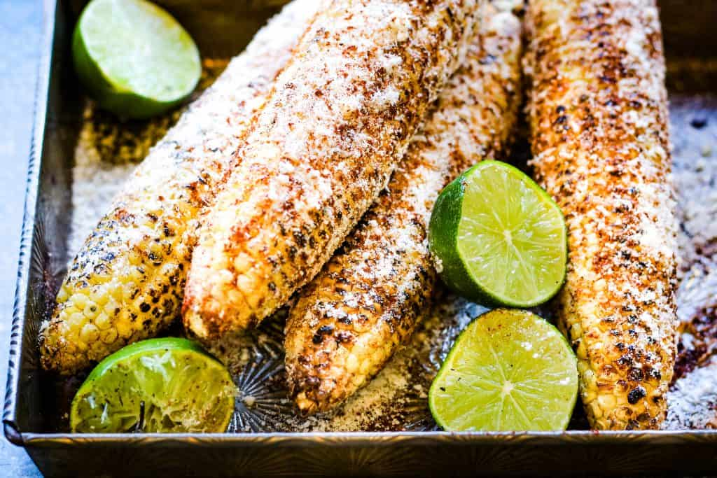 metal baking pan with elote, Mexican grilled corn cobs with mayonnaise, chili powder, lime juice, and grated cheese