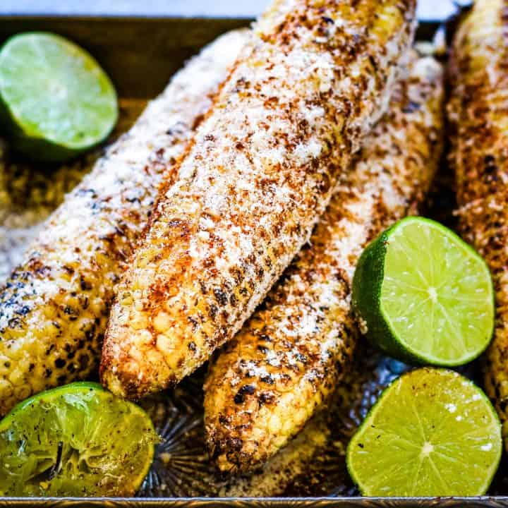Low angle shot of grilled Mexican corn with limes, sprinkled with chili powder and grated cheeese