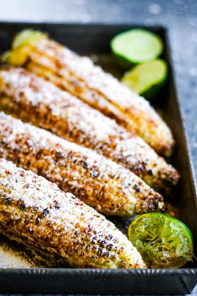 low angle vertical shot of grilled Mexican corn with limes, cobs are coated with mayonnaise and sprinkled with chili powder and grated cheese