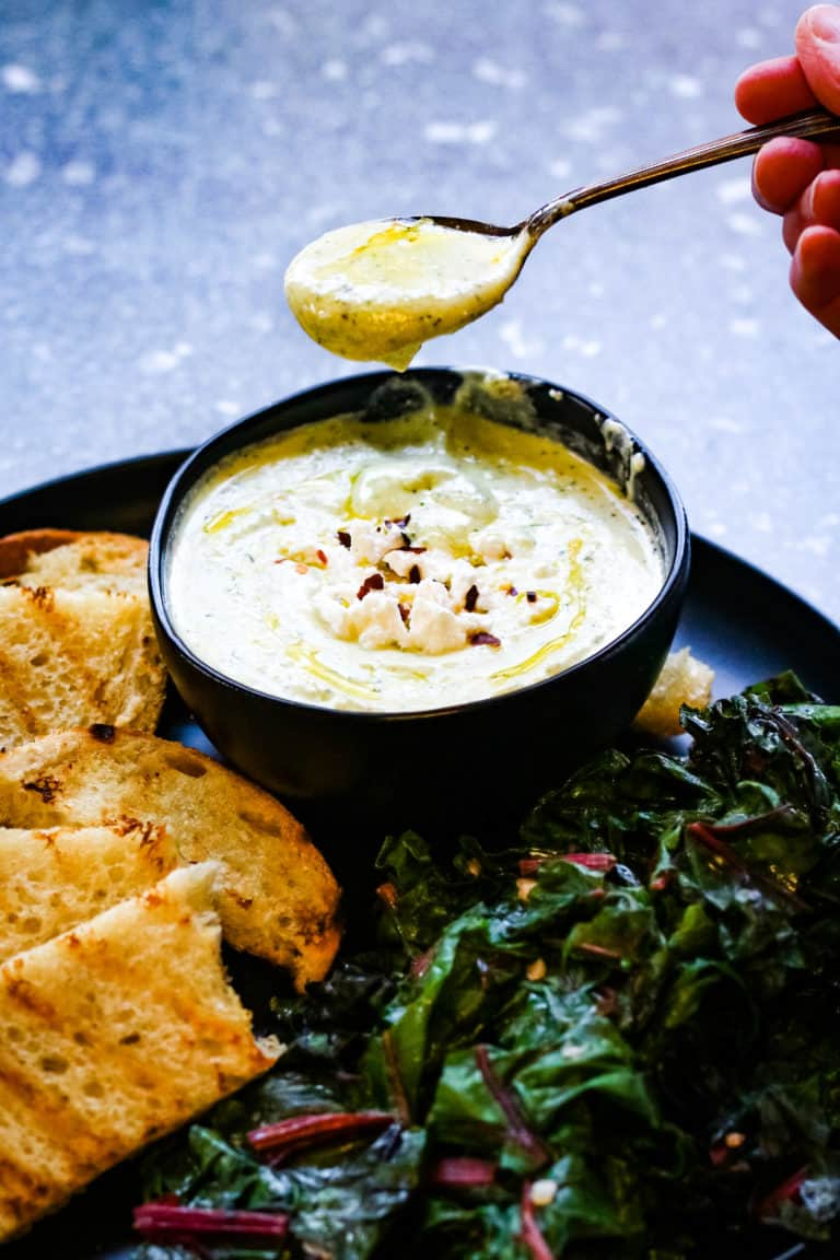 low angle shot of a black platter with grilled sourdough bread, sauteed chard, and a black bowl holding whipped feta spread. A spoonful of whipped feta spread is held above the bowl
