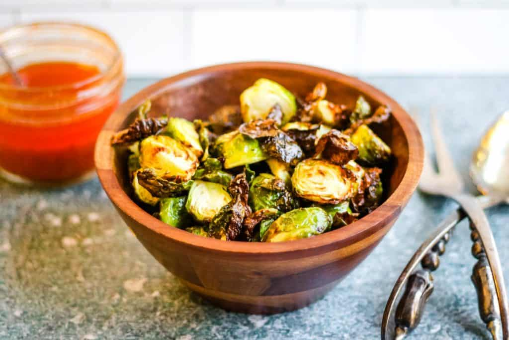 Air fried brussels sprouts, halved, browned, and crisp, in a wooden bowl. There is a jar of harissa dressing behind and to the left and a pair of silver salad servers on the table to the right.