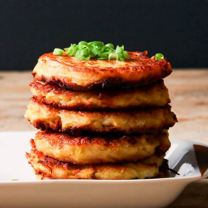 Low angle photo of a stack of 5 potato latkes on a white rectangular plate. There is a bowl of sour cream on the plate and both the sour cream and potato latkes are garnished with sliced green onions.