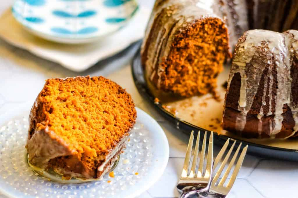 Low angle shot of a slice of pumpkin spice bundt cake on a plate. There is the full cake with a piece taken out of it behind on a platter and 2 forks next to the serving plate.