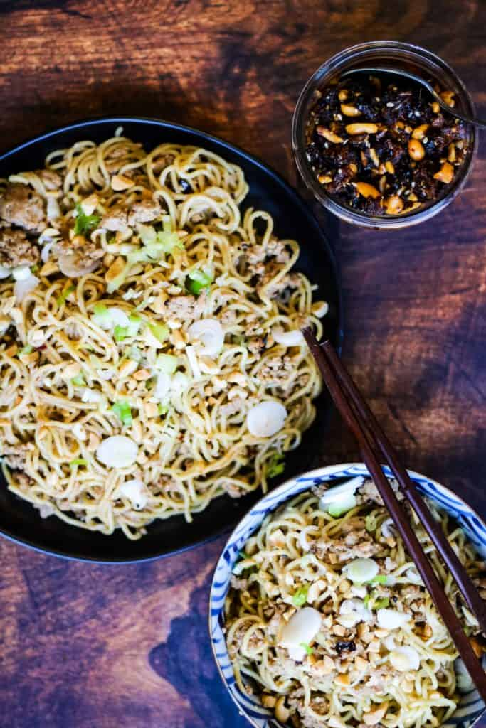 overhead shot of chinese sesame noodles on a black plate. Next to it is a blue and white serving bowl with sesame noodles in it and a pair of wooden chopsticks resting on the edge. There is also a jar of chile crisp. The table is dark brown wood.