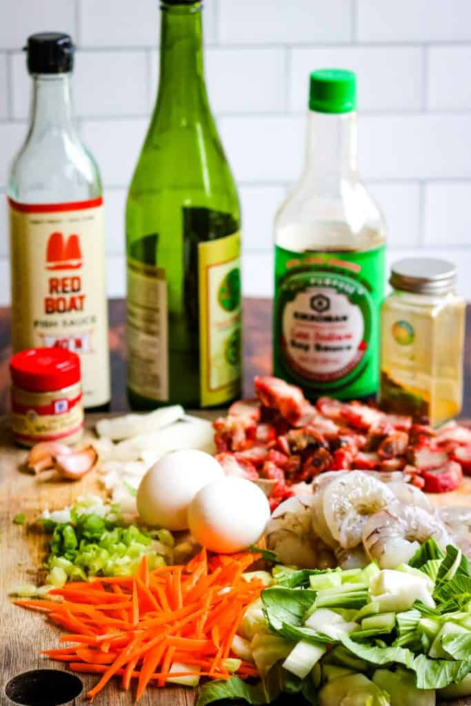 ingredients for singapore rice noodles shot from a low angle. Ingredients include fish sauce, sake, soy sauce, curry powder, white pepper, garlic, onion, eggs, char siu, julienned carrots, prawns, and bok choy