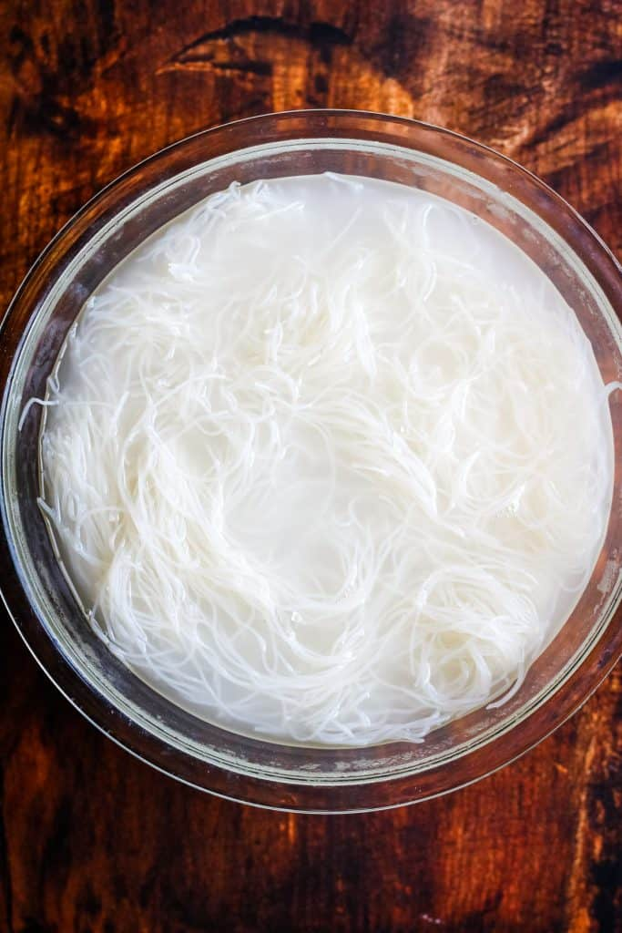 rice vermicelli soaking in a bowl of hot water, shot from overhead
