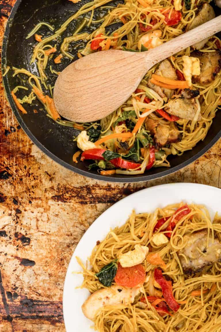 Overhead shot of a skillet of singapore noodles and a serving of the noodles on a plate.