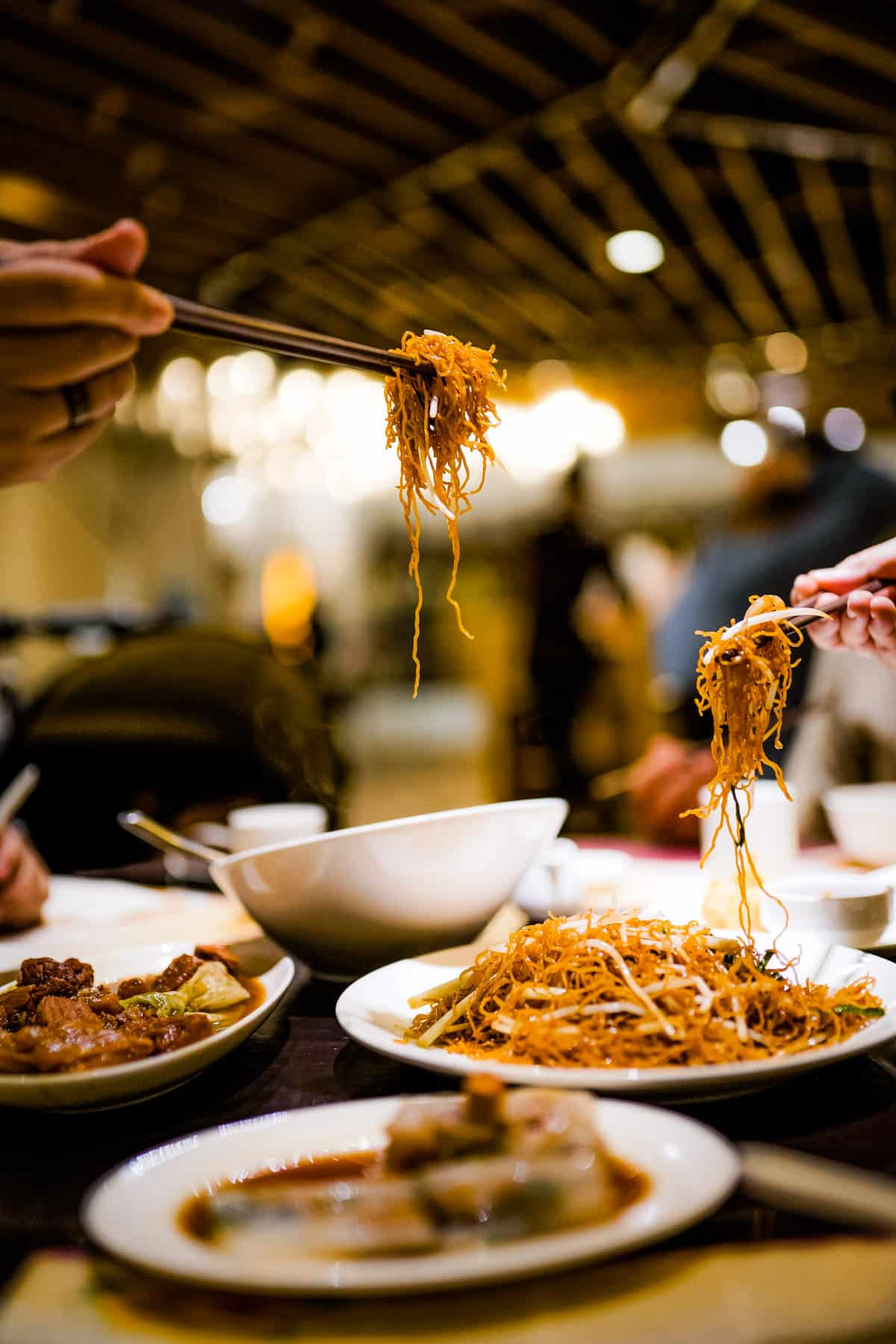 singapore rice noodles on a table in a restaurant with lots of other dishes. Two hands can be seen lifting noodles with chopsticks.
