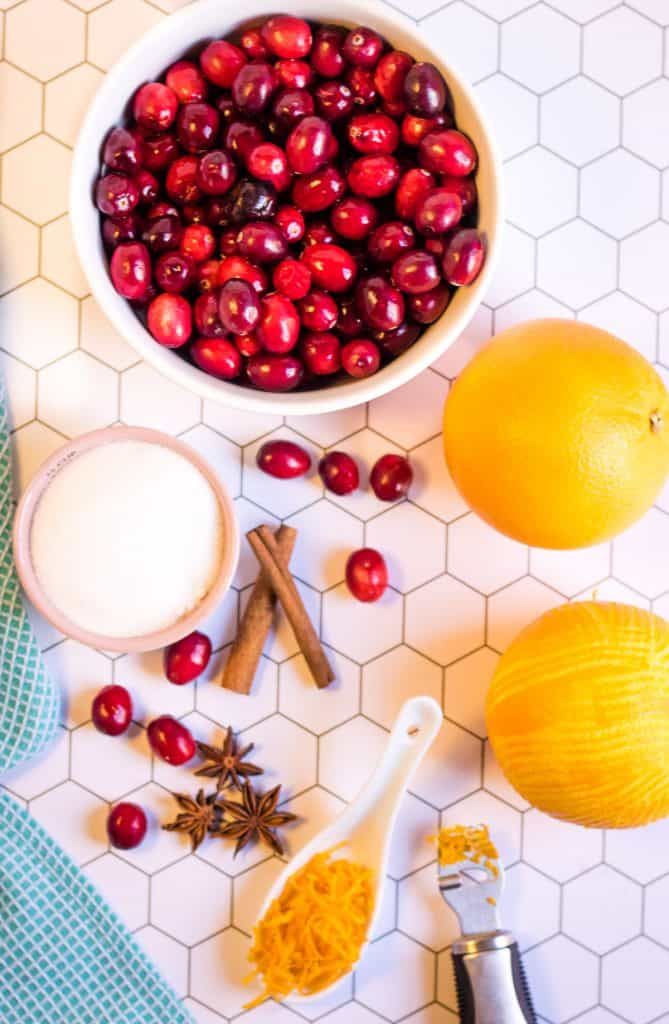 Overhead shot of ingredients to make cranberry sauce: cranberries, oranges, cinnamon sticks, star anise pods, and sugar.