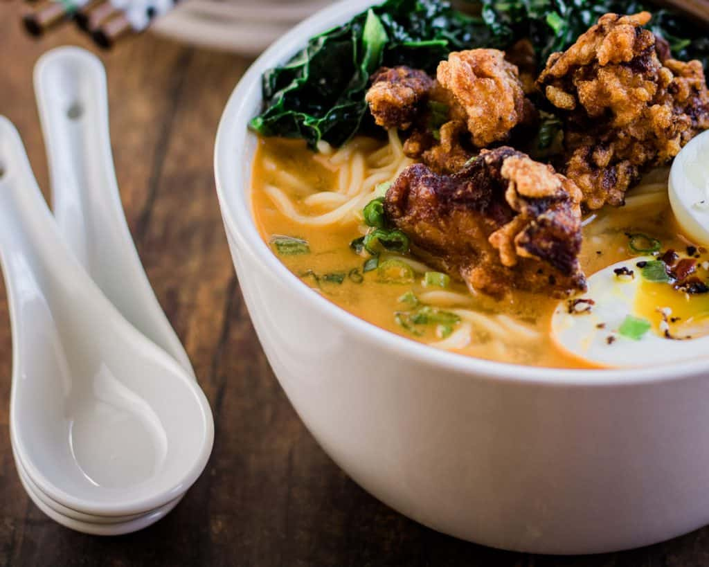 Low angle shot of a bowl of spicy miso ramen topped with chicken karaage, or Japanese fried chicken, soft boiled egg, and sauteed kale.