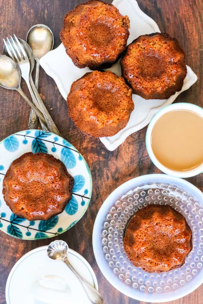 overhead shot of mini honey cake on plates with coffee and forks and spoons
