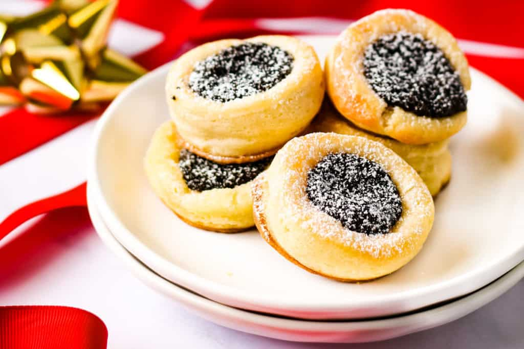 several poppy seed filled kolacky on a white plate with red and gold ribbons in the background.