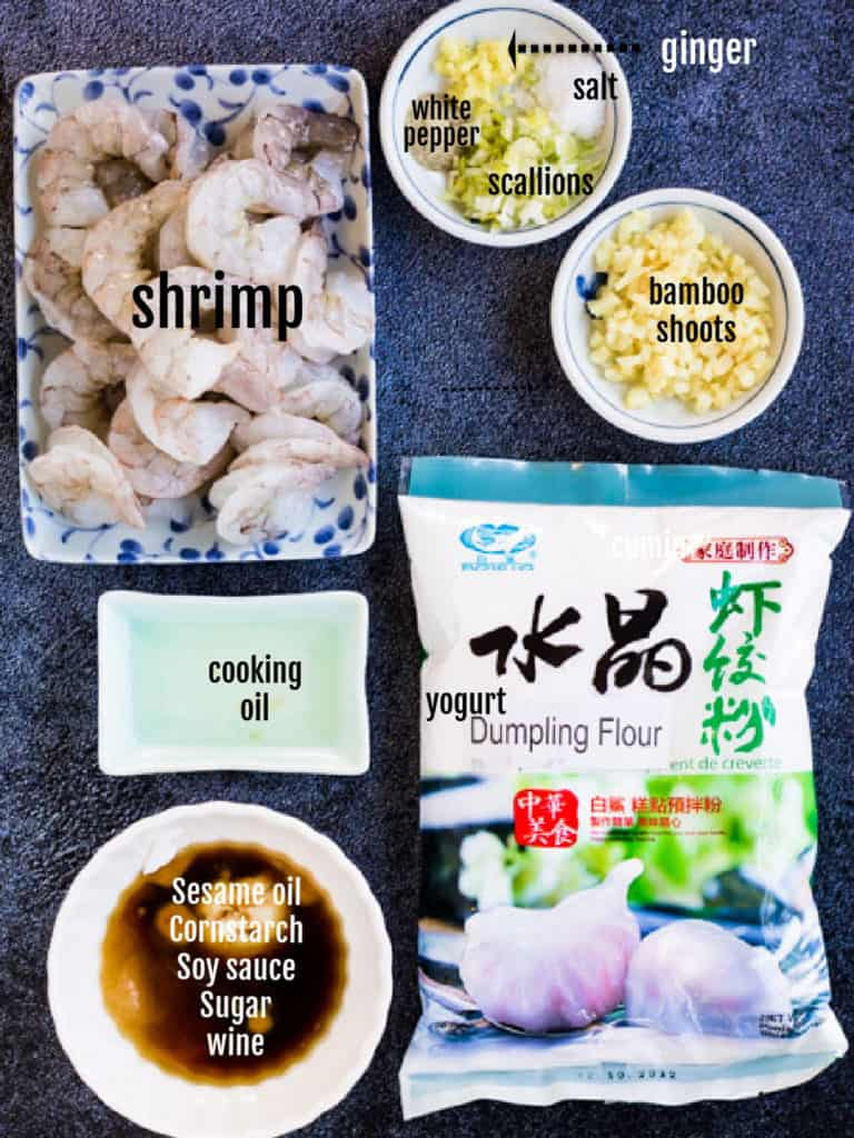Overhead shot of the ingredients needed: Shrimp, ginger, scallions, white pepper, salt, bamboo shoots, dumpling flour, cooking oil, sesame oil, soy sauce, cornstarch, sugar, wine