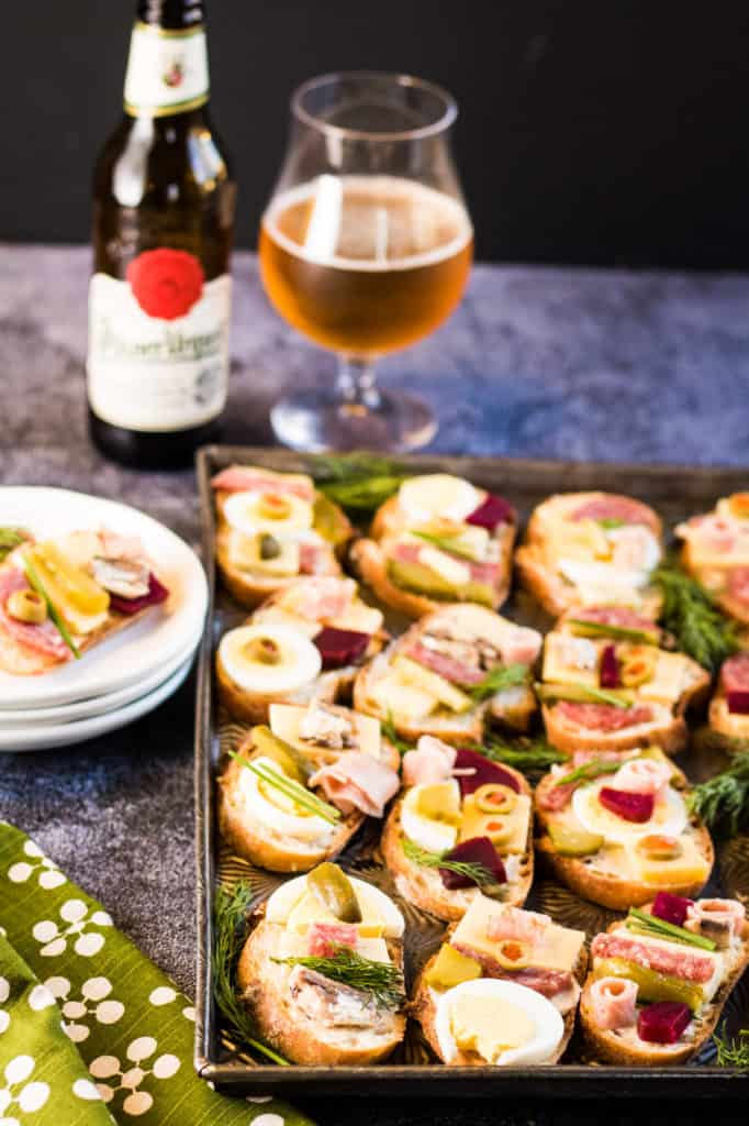 Low angle shot of a tray full of the sandwiches with a bottle of pilsner urquell beer and a glass of beer in the background.