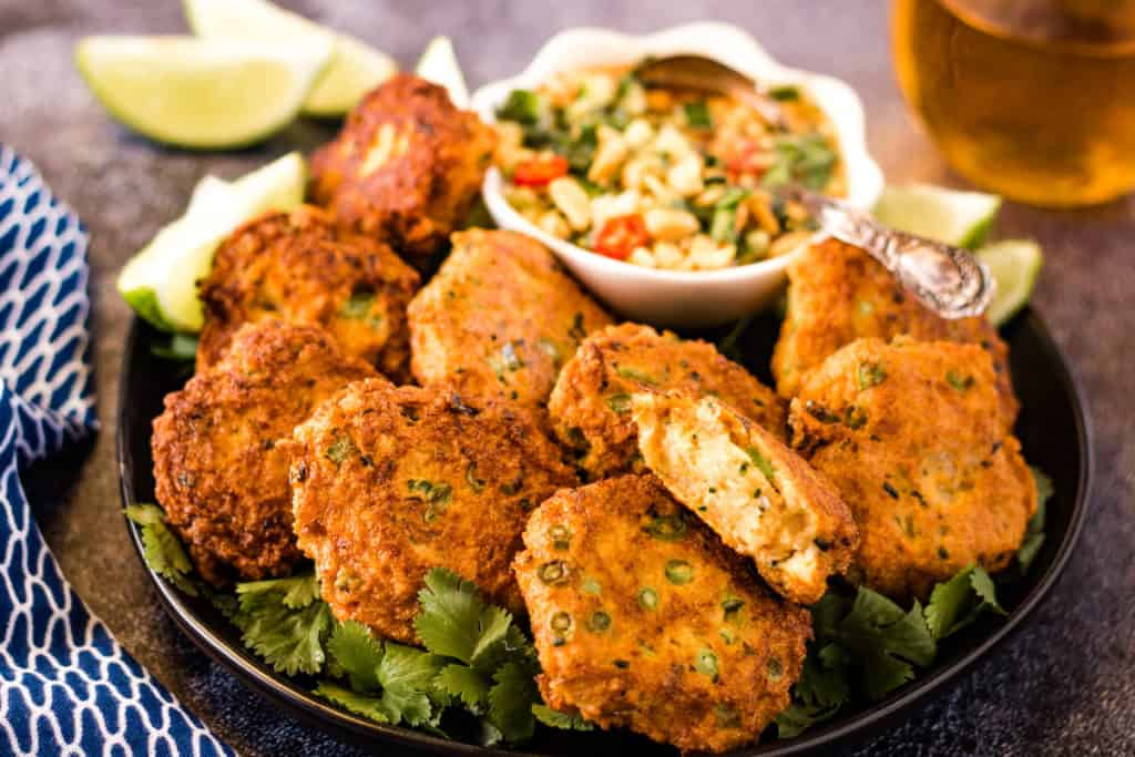 Thai fish cakes piled on a plate with a bowl of sweet chili dipping sauce and lime wedges in the background