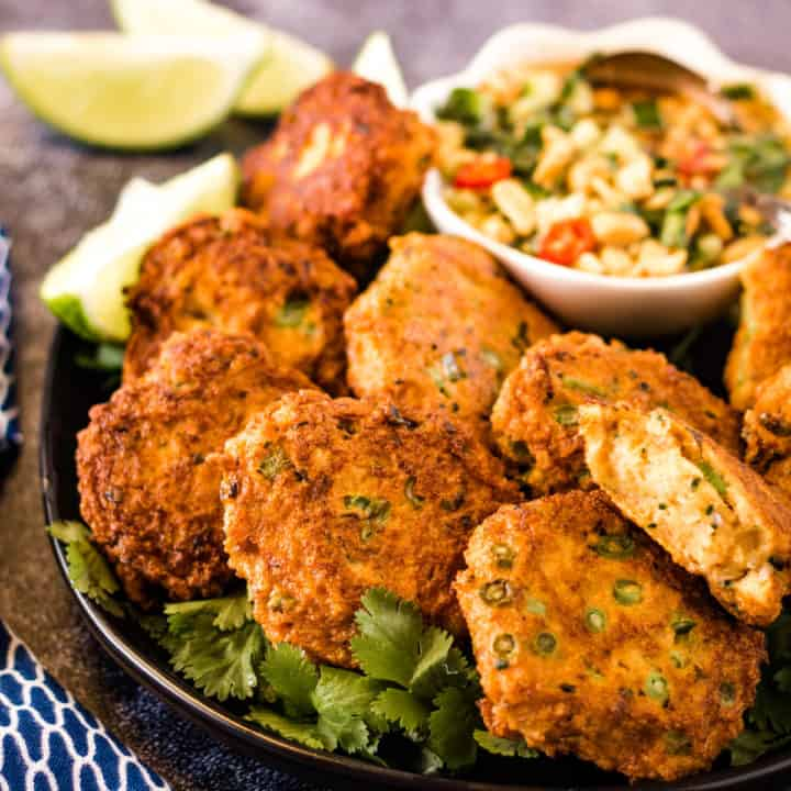low angle shot of fish cakes on a plate with dipping sauce and limes in the background