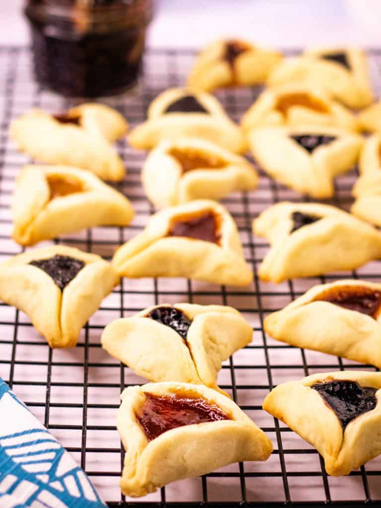 low angle shot of hamentashen cookies baked and cooling on a rack