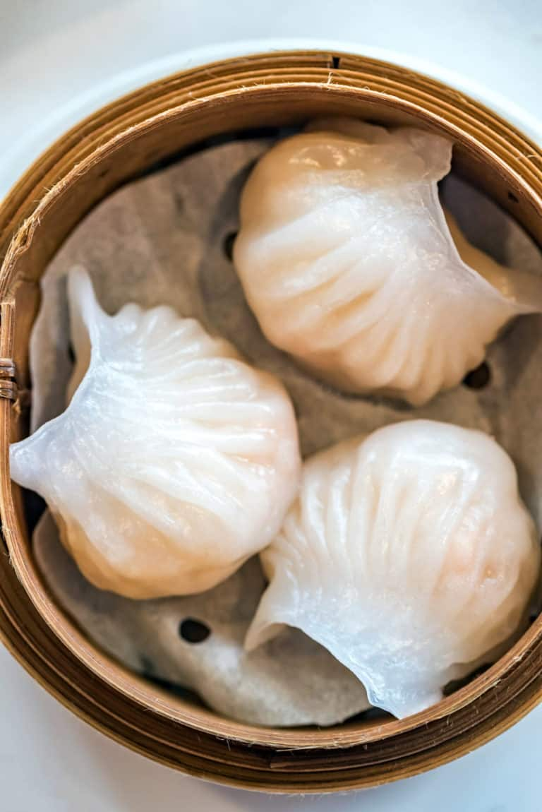 overhead shot of 3 har gow shrimp dumplings in a bamboo steamer basket