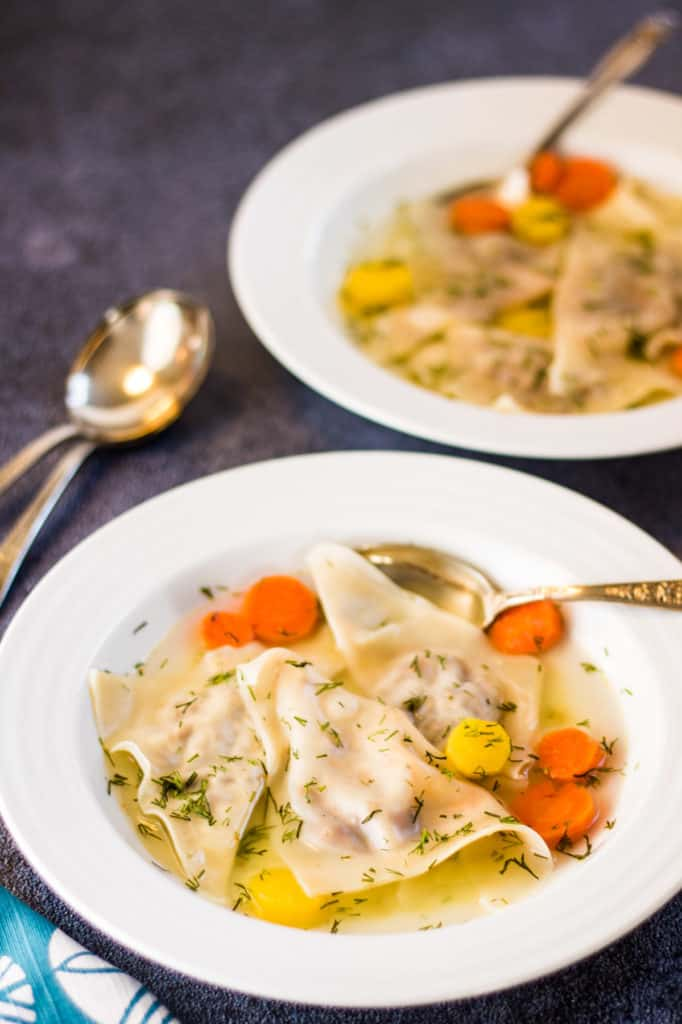 low angle shot of two bowls of broth with kreplach and carrots