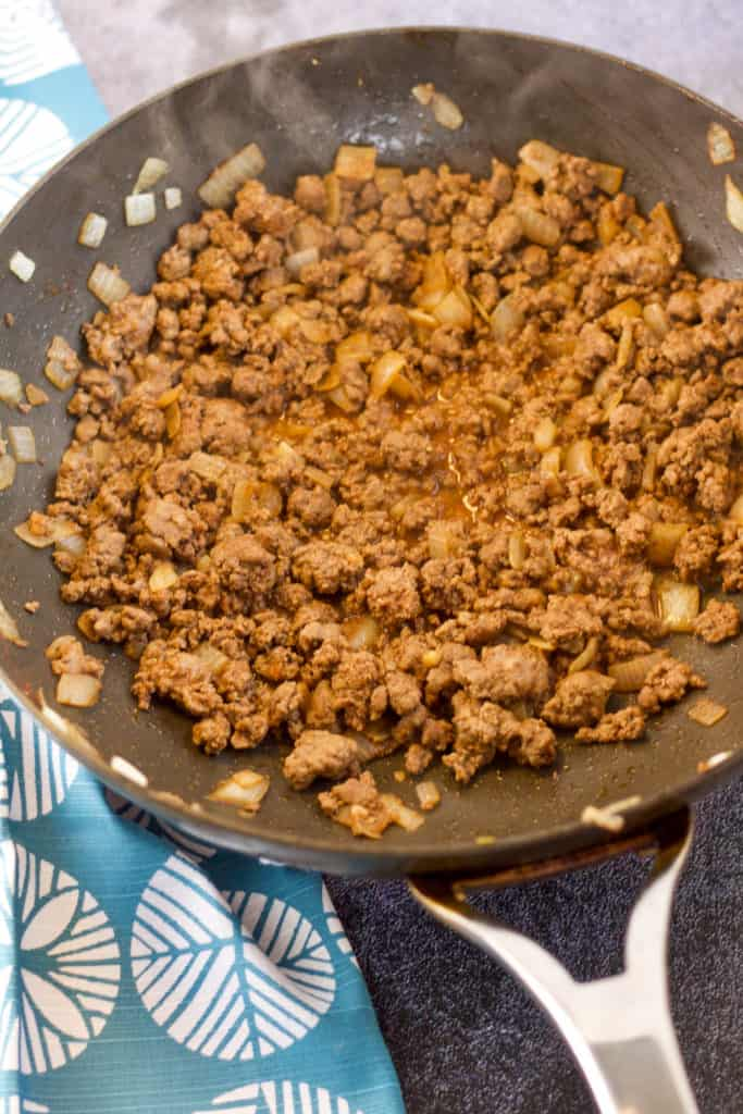 ground beef sauteed in a skillet with onions, garlic, salt, pepper, and paprika