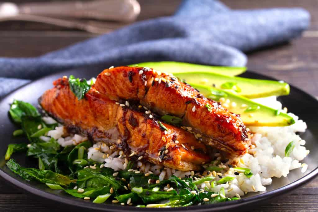 low angle shot of the cooked miso glazed salmon on a black plate. The salmon is on a bed of white rice with sliced avocado and sauteed spinach and is garnished with sesame seeds.