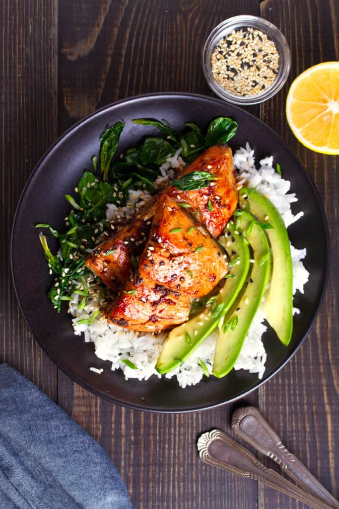 Overhead shot of the cooked miso glazed salmon. There is a black plate with a bed of white rice, the fish on top of the rice with sliced avocado and sauteed spinach on the side. Garnished with sesame seeds.