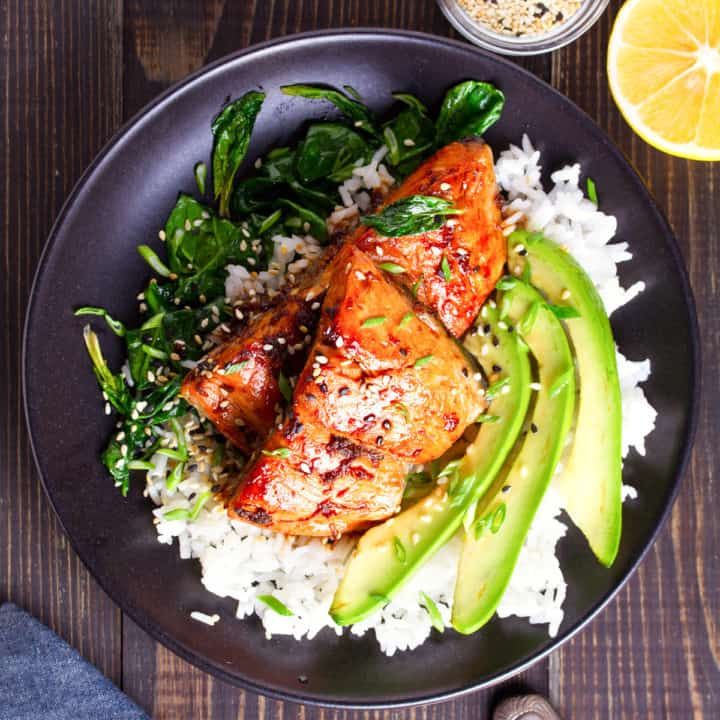 Overhead shot of the dish. There is a black plate with a bed of white rice, the fish on top of the rice with sliced avocado and sauteed spinach on the side. Garnished with sesame seeds.