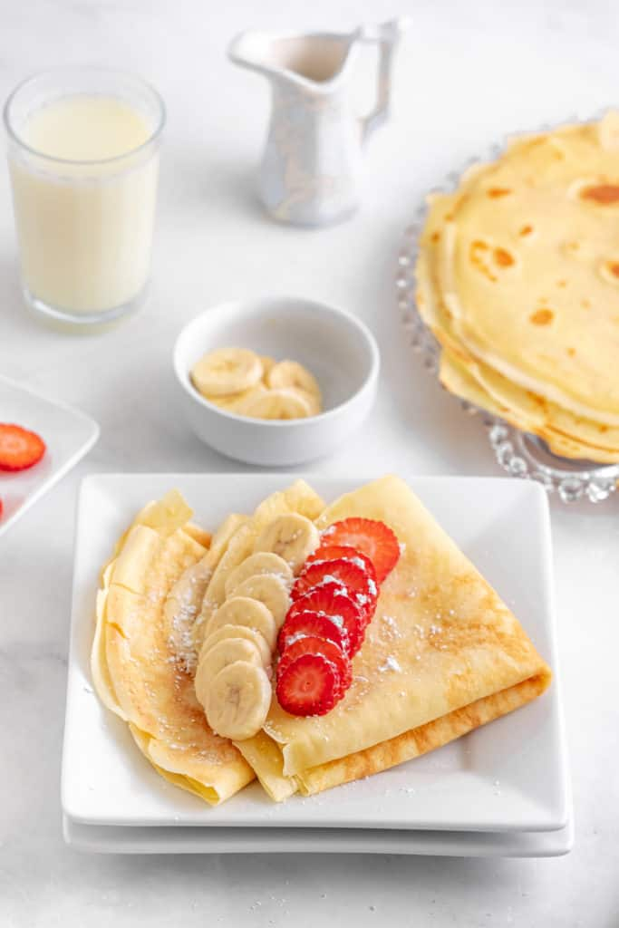 Low angle shot of crepes folded on a square plate with strawberries and bananas on top with a bowl of banana slices and a stack of cooked crepes in the background.