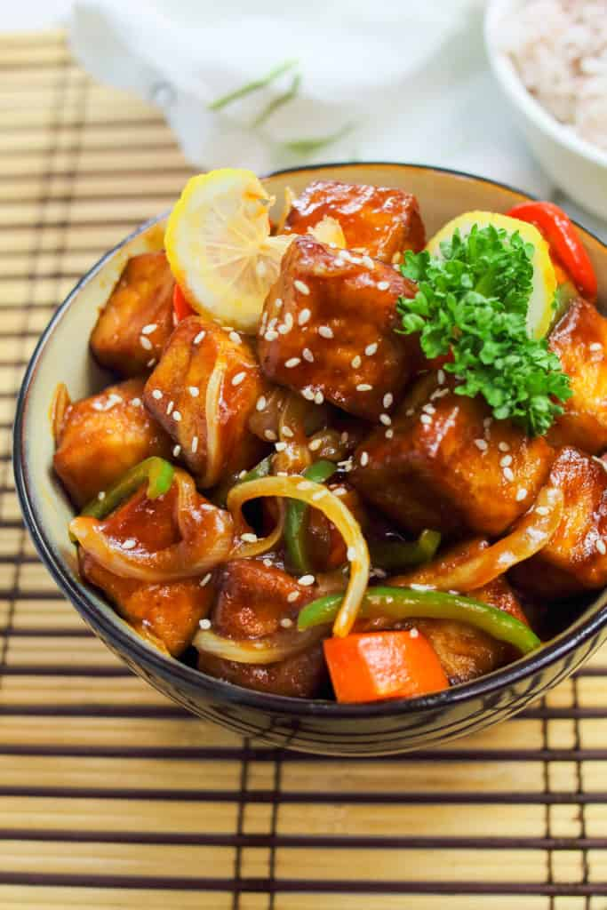 Low angle shot of vegetarian sweet and sour tofu in a bowl.