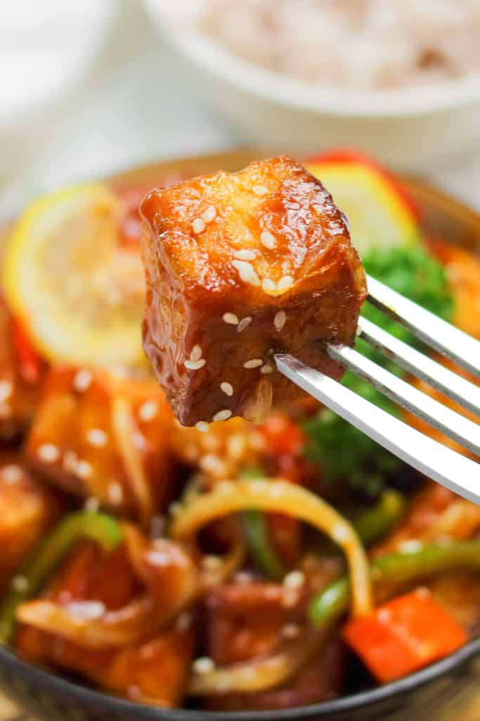 Close up of a fried tofu cube in sweet and sour sauce on a fork.