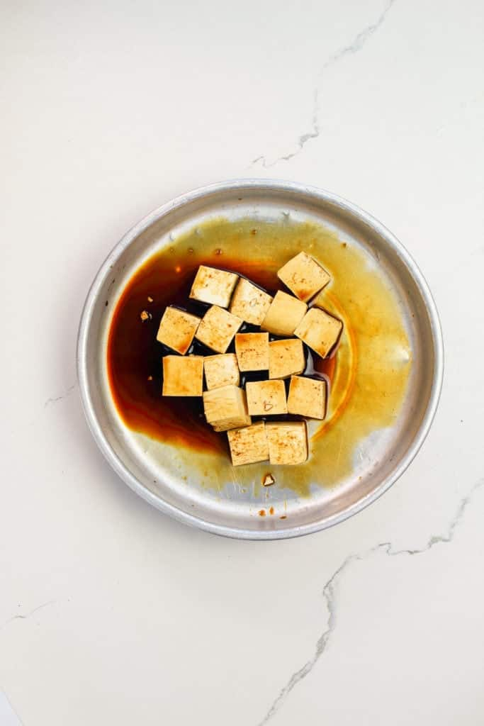 Tofu cubes in a bowl, marinating in a mixture of soy sauce and black rice vinegar, shot from overhead.