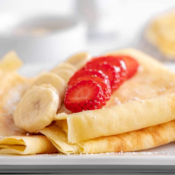 Low angle photo of folded crepes with sliced banana and strawberry on top.