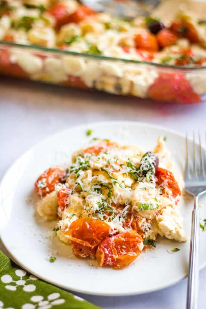 pasta with tomatoes, feta cheese, olives, and basil on a white plate, shot from a low angle.