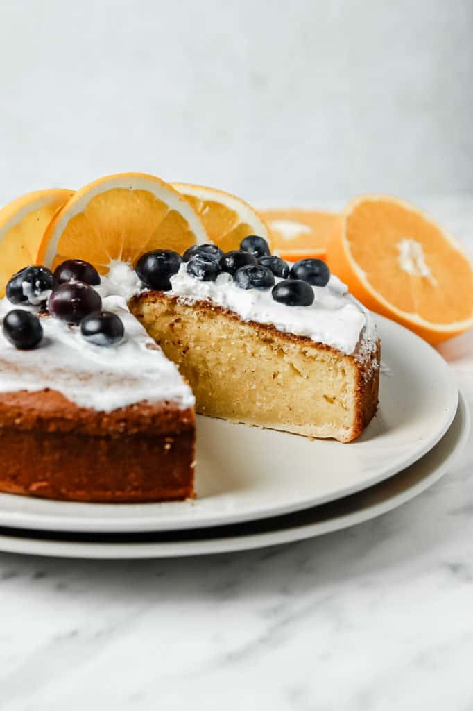 Low angle shot of the whole cake minus one slice. The cake as whipped cream, blueberries, and orange slices on top.