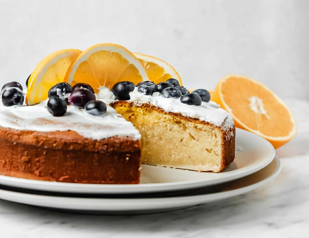 low angle shot of the orange sponge cake with a slice removed. It is topped with whipped cream, blueberries, and orange slices.