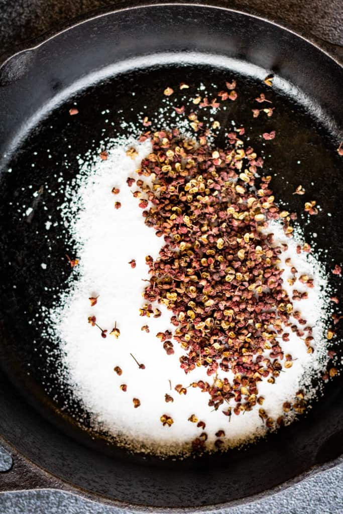 Overhead shot of Szechuan peppercorns and kosher salt in a cast-iron skillet.
