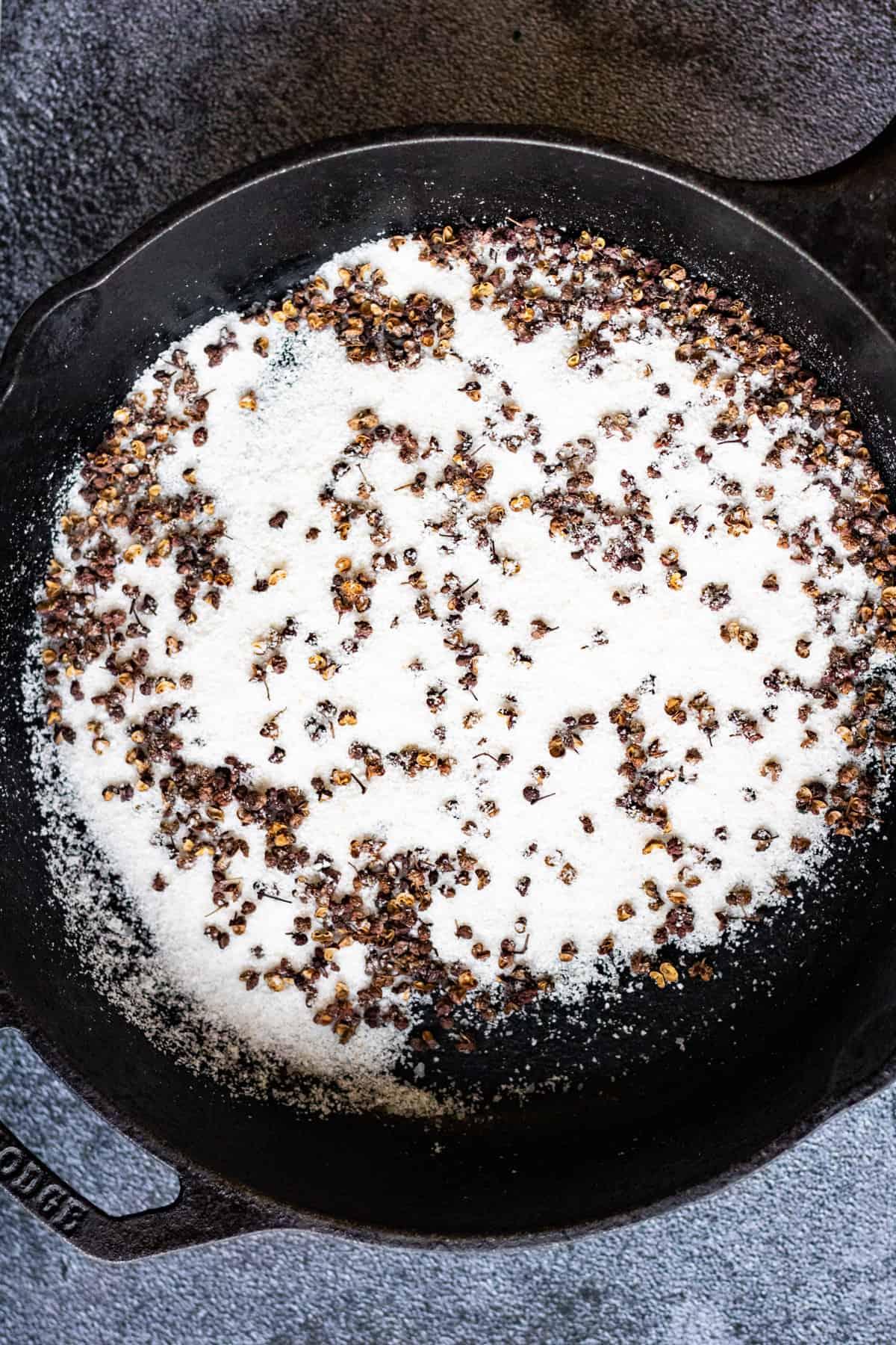 Overhead shot of Szechuan peppercorns and kosher salt in a cast-iron skillet.