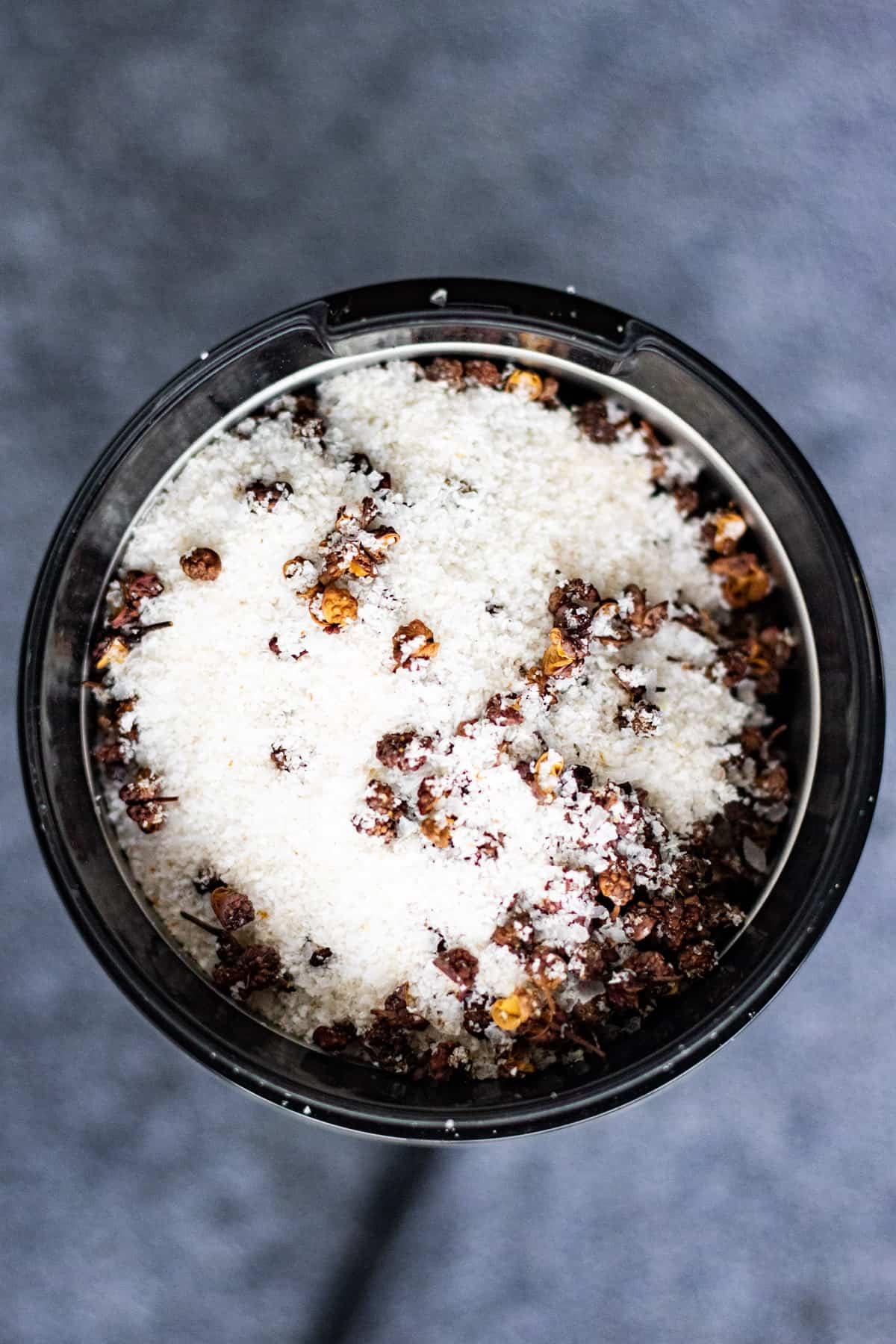 Overhead shot of Szechuan peppercorns and kosher salt in a spice grinder.